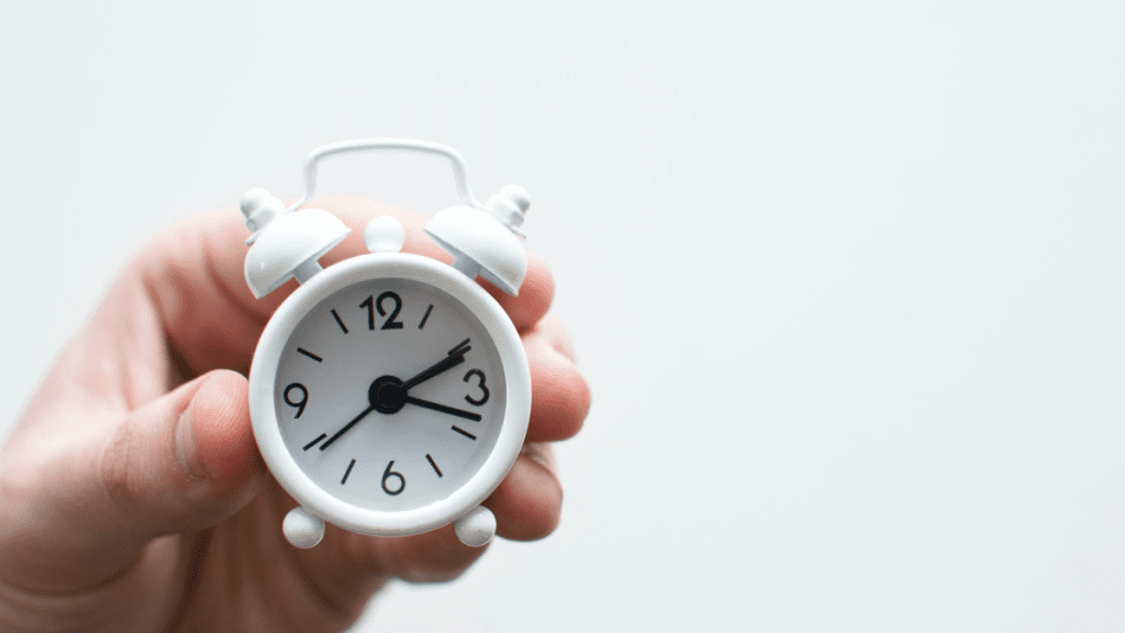 a person holding a small alarm clock